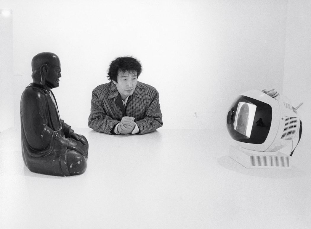 Nam June Paik with Buddha TV (1974) at Projects: Nam June Paik, Museum of Modern Art, New York, 1977. © Eric Kroll.